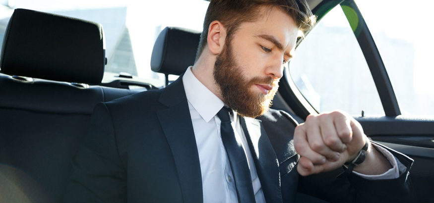 Confident young businessman looking at his watch while sitting on the back seat of a car